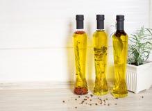 Tre bottiglie di olio d'oliva con le spezie Fotografia Stock Libera da Diritti