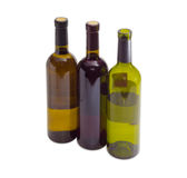 Tre bottiglie di vario vino su un fondo leggero fotografia stock libera da diritti