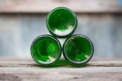Tre bottiglie di vetro, fondi verdi si trovano avanti su di legno Immagini Stock Libere da Diritti