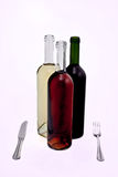 Tre bottiglie di vino con la lama e la forcella. fotografia stock