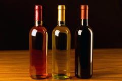 Tre bottiglie di vino sulla tavola di legno e sul fondo nero Fotografie Stock Libere da Diritti
