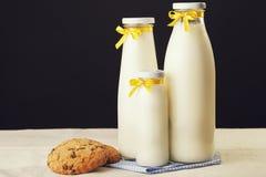 Tre bottiglie per il latte con il nastro giallo e biscotti su un BAC nero Fotografia Stock Libera da Diritti