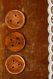 Tre bottoni di legno fatti a mano sulla vecchia tavola Fotografia Stock Libera da Diritti
