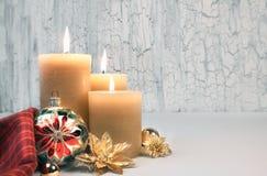 Tre brännande stearinljus med guld- julpynt på lantlig neutral bakgrund Royaltyfria Foton