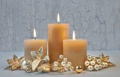 Tre brännande stearinljus med guld- julpynt på rusti Fotografering för Bildbyråer