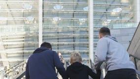Tre bröder som uppför trappan kör till stadion, fotbollsfan, stöttande lag arkivfilmer