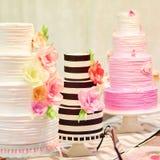 Tre bröllopstårtor på en efterrätttabell Royaltyfri Foto