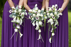 Tre brudtärnor som rymmer bröllopbuketter Royaltyfri Foto