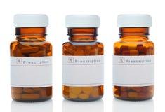 Tre bruna medicinflaskor med olika droger Royaltyfri Bild