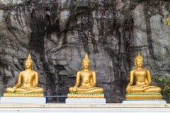 Tre Buddha che si siede con il fondo della parete di pietra Immagini Stock