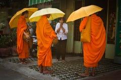 Tre buddistiska munkar välsignar en äldre dam i Phnom Phen, Cambod Royaltyfri Bild