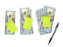 Tre buntar av dollar med anmärkningar och pennan Arkivbild