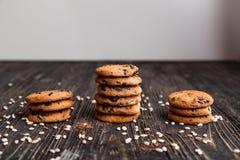 Tre buntar av knapriga choklade kakor på en mörk trätabell Royaltyfria Foton