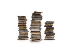 Tre buntar av mynt som isoleras på vit Royaltyfria Bilder