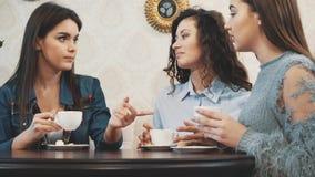 Tre buone giovani amiche si sono incontrate in un caffè Durante questo della bevanda cappuccino simultaneamente Abbia capelli ner video d archivio