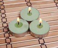 Tre burning stearinljus på matt bambu Fotografering för Bildbyråer