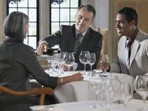 Tre Businesspeople som sitter på restaurangtabellen royaltyfri foto