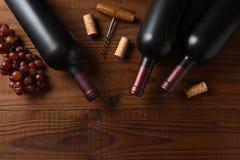 Tre Cabernet - sauvignon vinflaska tvärt från direkt över på en mörk trätabell med druvakorkar och korkskruv och kopia royaltyfri foto