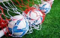 Tre calci di calcio nel concetto di sport della rete di addestramento Immagini Stock Libere da Diritti