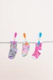 Tre calzini dei bambini sulla linea di lavaggio fotografia stock libera da diritti