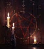 Tre candele brucianti e plance di legno con il pentagramma Fotografia Stock Libera da Diritti