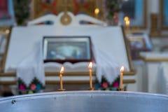 Tre candele della cera su una grande ciotola con acqua per il battesimo del bambino fotografie stock libere da diritti