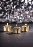 Tre candele dorate di arrivo accese con il fondo del bokeh Fotografia Stock