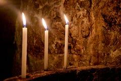 Tre candele nella linea Fotografia Stock