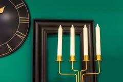 Tre candele su un fondo verde, sulla parete un orologio e una struttura Immagine Stock Libera da Diritti