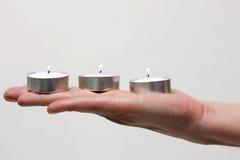 Tre candele su una mano Fotografia Stock Libera da Diritti
