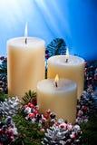 Tre candele in una disposizione di fiore di avvenimento Fotografie Stock