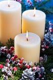 Tre candele in una disposizione di fiore di avvenimento Fotografie Stock Libere da Diritti