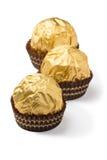 Tre caramelle di cioccolato isolate in stagnola dorata Immagine Stock