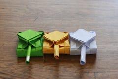 Tre carri armati di origami su un piano d'appoggio di legno Immagini Stock Libere da Diritti