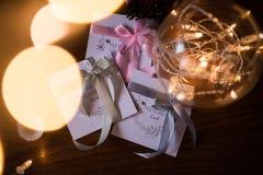 Tre carte del photoshoot del regalo con i nastri variopinti vicino alla ghirlanda delle luci nel vaso Fotografia Stock Libera da Diritti