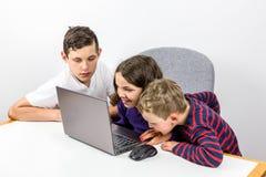 Tre Caucasian barn som tillsammans använder bärbara datorn, förträning till tidig tonår härlig för studiokvinna för par dans skju royaltyfria foton