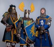 Tre cavalieri medioevali nella condizione completa dell'armatura Fotografia Stock