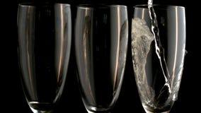 Tre champagneflöjter med en som fylls stock video