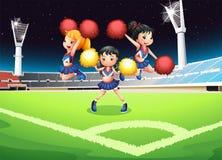 Tre cheerdancers che eseguono nel campo di calcio Fotografia Stock
