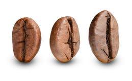 Tre chicchi di caffè arrostiti stanno dritti Macro Fondo isolato bianco fotografia stock