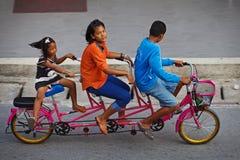 Tre childred sulla bicicletta in tandem su una strada Immagine Stock