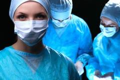 Tre chirurghi al funzionamento del lavoro nel paziente chirurgico di risparmio del teatro e ad esaminare il monitor di vita Medic Fotografia Stock