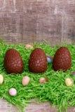 Tre chokladägg och vaktelägg på ett grönt gräs framme av en träbakgrund tillgänglig hälsning för korteaster eps mapp Royaltyfri Bild