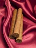 Tre cigarrer på röd satäng Arkivfoton