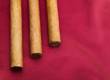 Tre cigarrer på röd satäng Arkivfoto