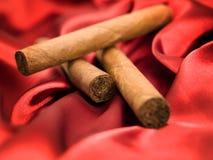 Tre cigarrer på röd satäng Arkivbild