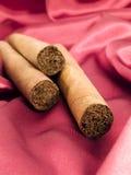 Tre cigarrer på röd satäng Royaltyfria Bilder