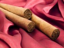 Tre cigarrer på röd satäng Royaltyfri Fotografi