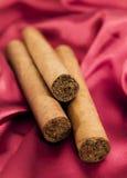 Tre cigarrer på röd satäng Royaltyfria Foton