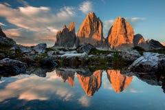 Tre Cime di Lavaredo met bezinning in meer bij zonsondergang, Dolomit stock foto